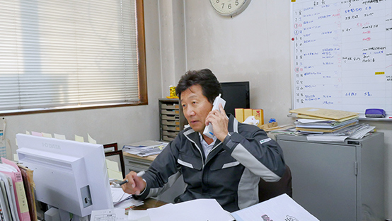本社事務所内にて板津和博社長が実際に仕事をしているシーン