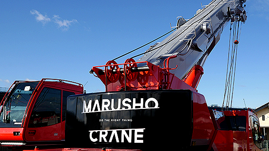 丸正クレーン作業株式会社の何曜倉庫に停車中の大型クレーンを背後から撮影した写真