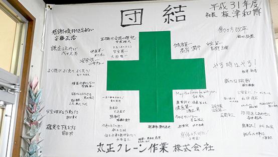 丸正クレーン作業所の事務所入り口に掲げてあった、安全を祈願した社員の寄せ書きフラッグ