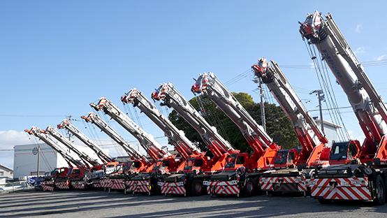 丸正クレーン作業所の南陽営業所に整然と並ぶ十数台の大型クレーンの写真